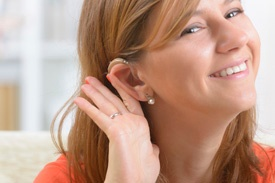 Lady holding hearing aid behind ear